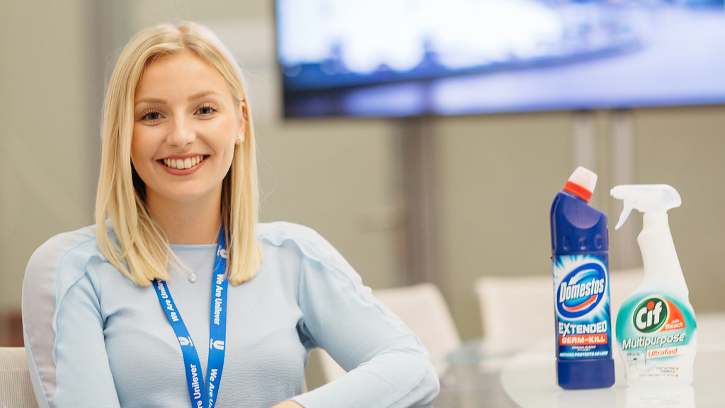 Madeline sitting at a table, smiling, with a bottle of Domestos and some CIF cleaning spray.
