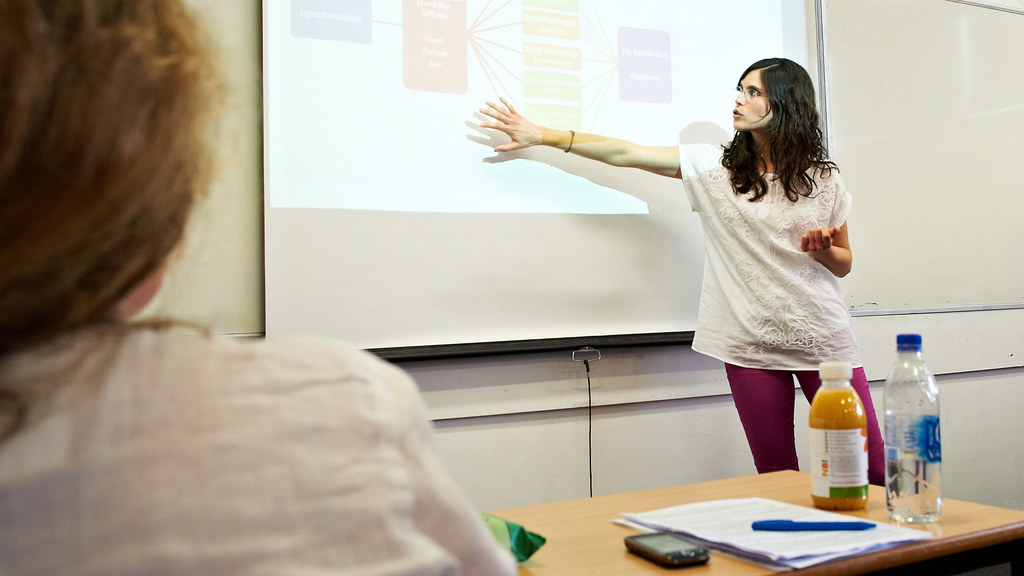 A lecturer gesturing at a chart on the whiteboard
