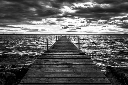 canon water pier blackandwhite blackwhite desaturated madison wisconsin burrowspark park maplebluff dock wood lake lakemendota summer sunset sunlight goldenhour clouds strangeclouds tranquil serenity peaceful calm tide waves unitedstates rocks shore shoreline