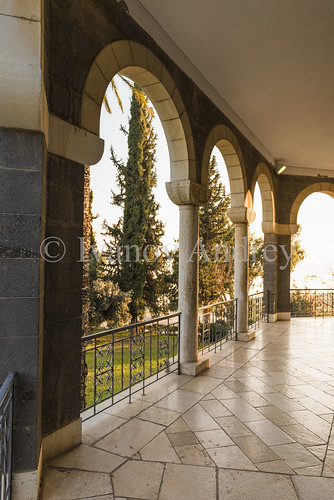 church christianity orthodoxy religion prayer cross colonnade row column evening sunset sun arch shadow light fence terrace tree plant space outdoor color concept emotion directline stone block brick wall building architecture history archaeology ancient angle vertical horizontal perspective theseaofgalilee israel