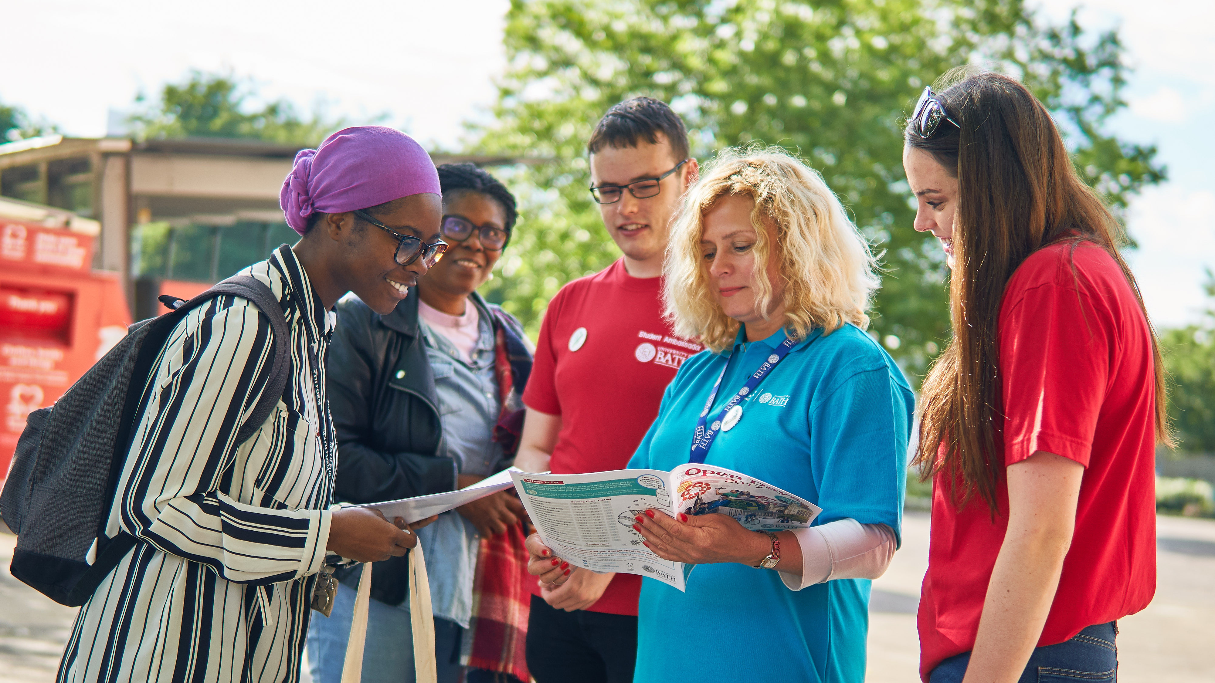 Two visitors get help from a student ambassador at a campus open day