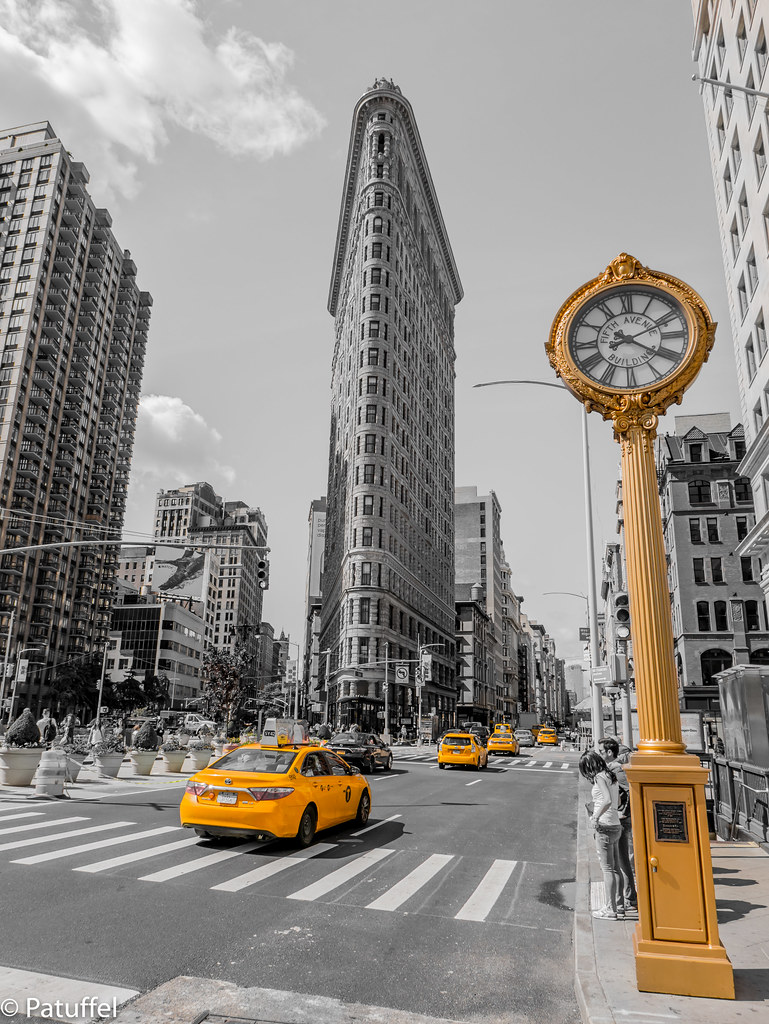 Yellow taxis and Golden Clock at the Flatiron Building in New York