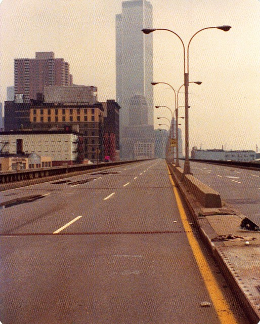 Just another day walking south toward the World Trade Center on the abandoned West Side Highway in Tribeca before there was a Tribeca. The brand new Independance Plaza North to the left of the Twin Towers. New York. June 1974
