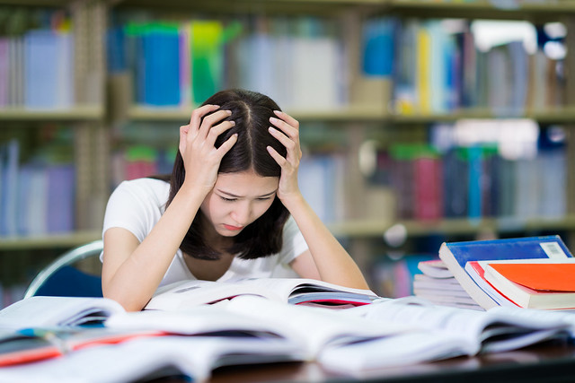 Asian lady student read a book before examination