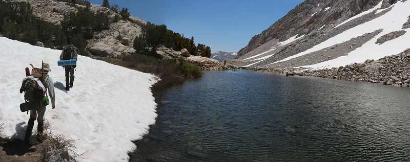 Hiking on the Paiute Pass Trail on the snow next to a small pond