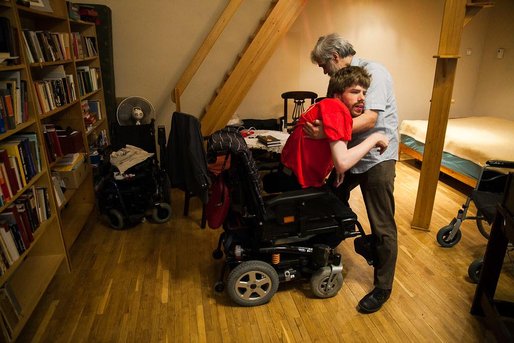 Vincét a szomszédban lakó édesapja ülteti át az elektromos székébe, amivel a városban közlekedni tud | Fotó: Magócsi Márton