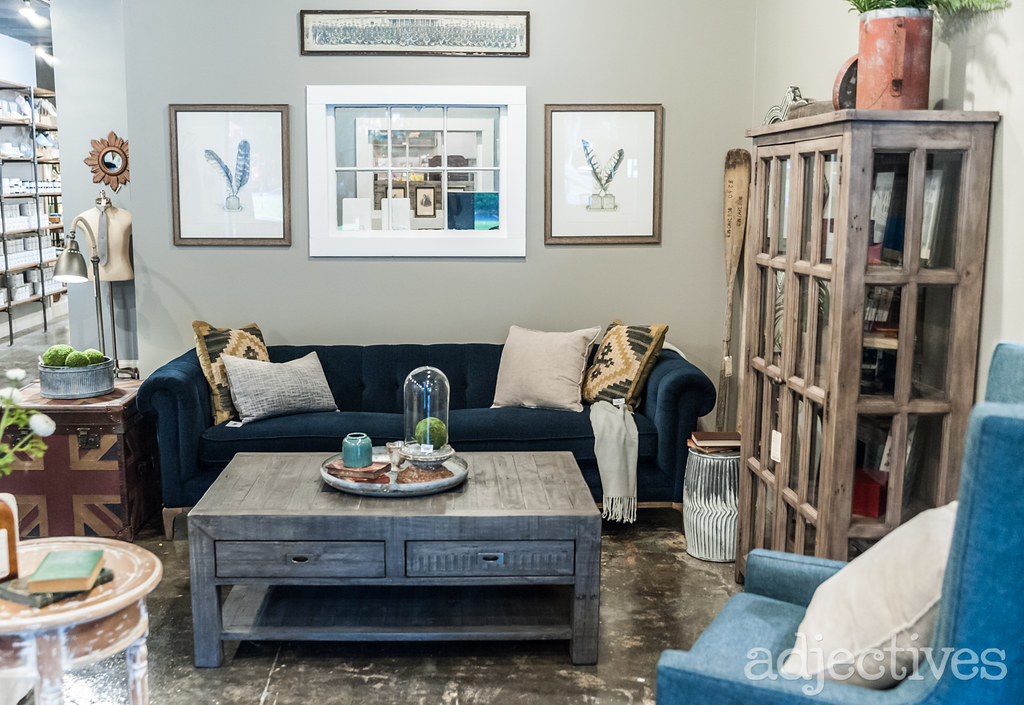 Blue sofa and rustic wood coffee table with living room furniture and home decor at Adjectives Altamonte