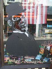 Comedy star Oliver Hardy looking out of a shop window.