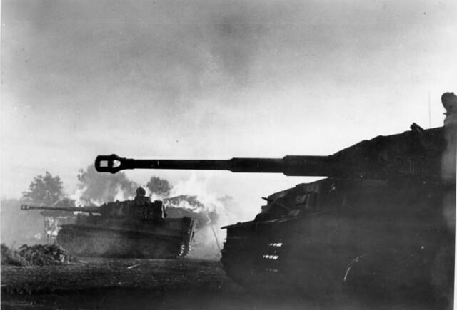 """Νοτίως του Ορέλ, επίθεση αρμάτων μάχης Panzer Mk VI """"Tiger"""", στο παρασκήνιο ένα φλεγόμενο κτίριο."""