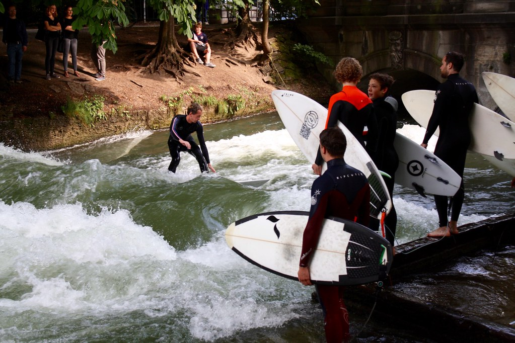Surfers ride a standing wave on the Eisbach in Munich's Englischer Garten. Copyright 2017 Jonny Eberle.