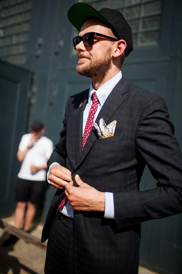 黒キャップ×黒チェックスーツ×ライトグレーシャツ×赤小紋柄ネクタイ