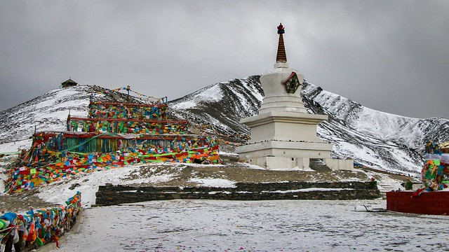 White stupa and prayer flags in Zheduo Mountain pass, elevation of 4298 meters 折多山の峠にて