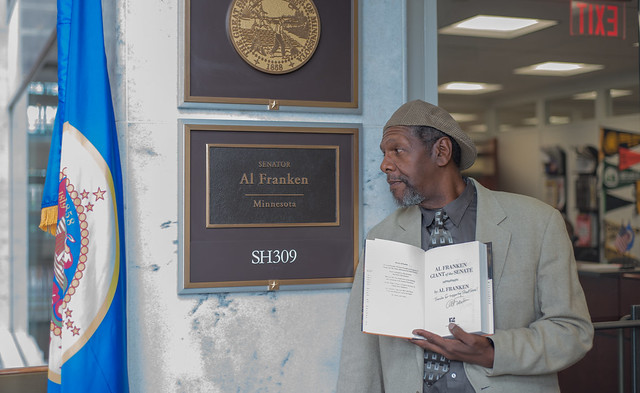 A photo of Ken Martin looking at the sign outside Sen. Franken's office