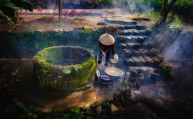 The older woman scoop water from water well in Son Tay district, Vietnam