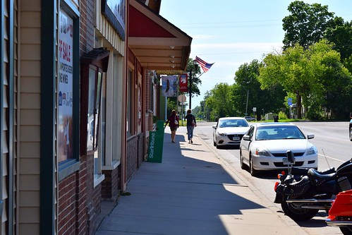 greyeagle minnesota smalltown rural mainstreet sidewalk motorcycles womenwalking sunnyday
