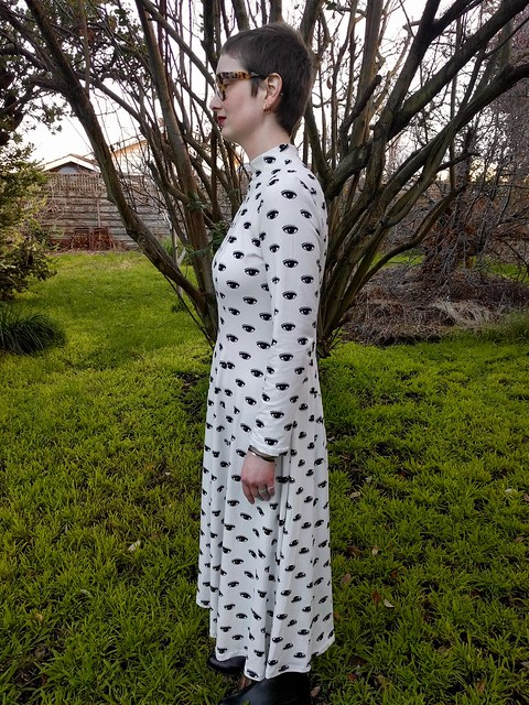 A woman stands in a garden. She is wearing a calf-length, full sleeve, high neck dress with black graphic eye print on white. She is smiling.