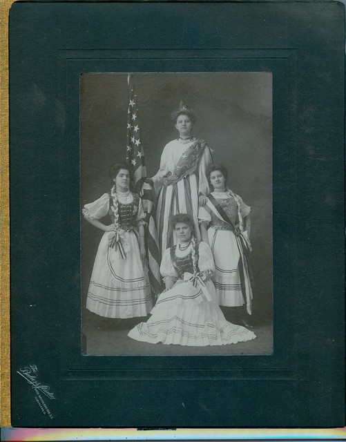 Women pose in costume with flag