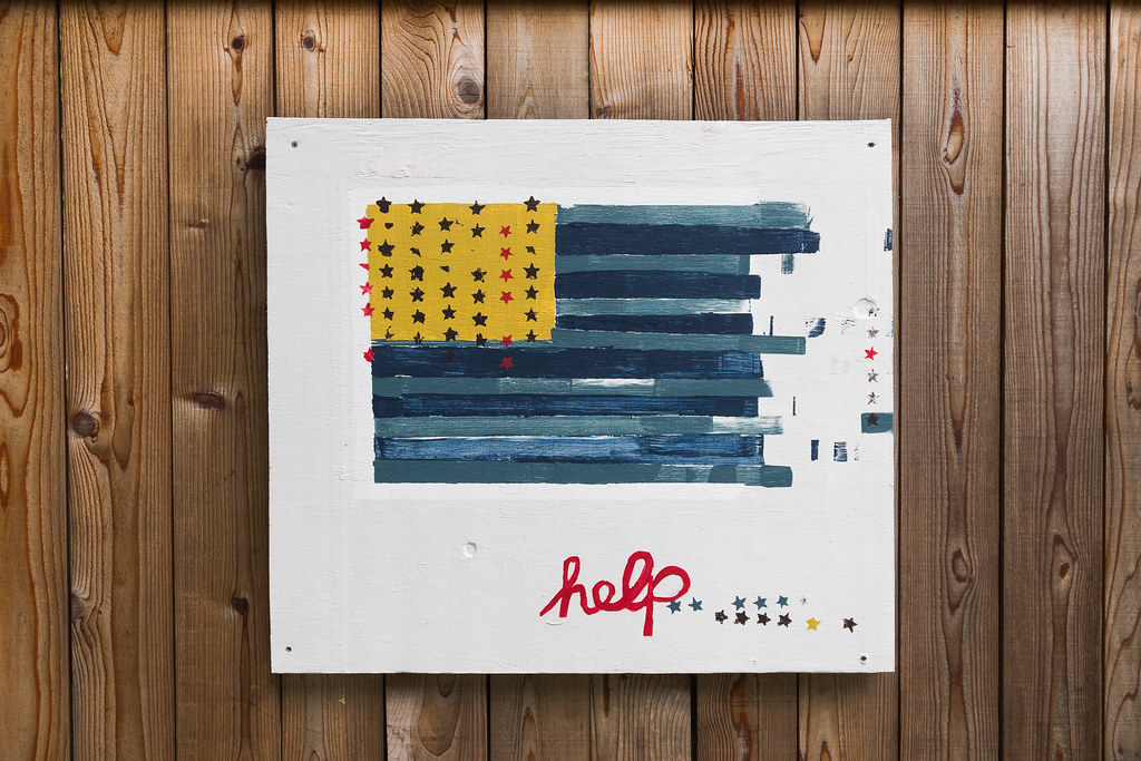 A painting of the United States flag with the word Help underneath