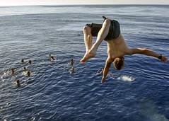 Sailor performs a backflip off USS Mahan during a swim call.