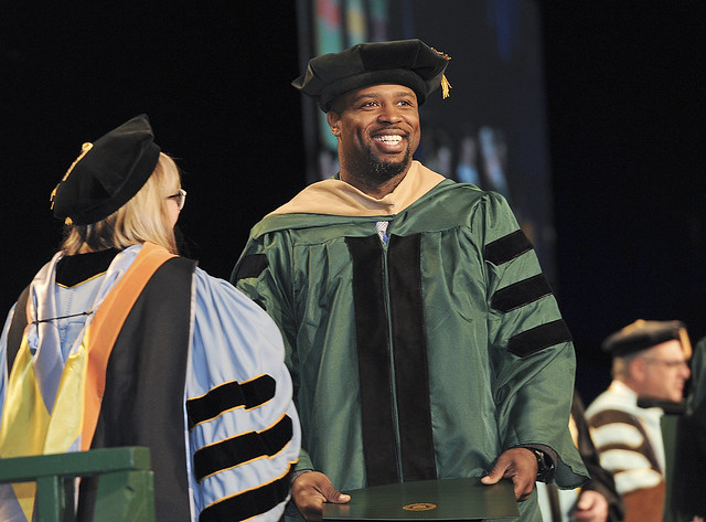 Dr. Sheila Sharbaugh (left) smiles at Dr. Jamar Purnsley after placing the traditional doctoral tam on his head. He received his degree as Doctor of Business Administration.