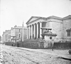 """""""Large public building, railings, steps, 6 columns in portico, 2 guns on plinths, one plinth inscribed India"""" is Tralee Courthouse"""