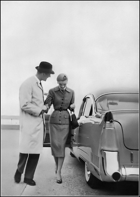 Model in black and white cashmere tweed suit by Ben Zuckerman, the car 1955 Cadillac Special Sixty, photo by Karen Radkai, Vogue, February 1, 1955