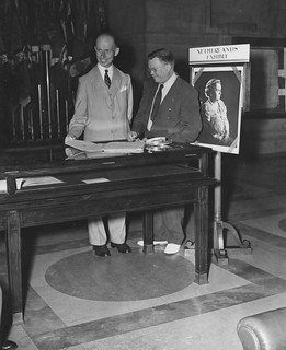 Photograph of the Ambassador of the Netherlands, His Excellency E. N. van Kleffens, and the Archivist of the United States, Dr. Wayne C. Grover, Examining the First Treaty to be Signed by the United States and the Netherlands