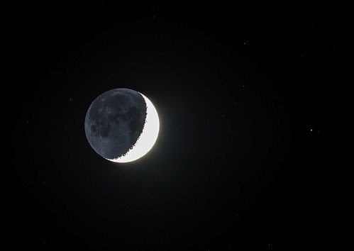 The Moon's Earthshine and Regulus in a starry background