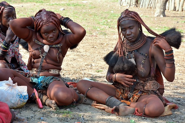 Himba women adjusting their hair - a Himba village in Opuwo, Namibia.