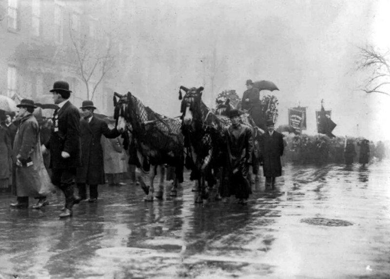 People and horses draped in black walk in procession in memory of the victims of the Triangle Shirtwaist Company fire, New York City