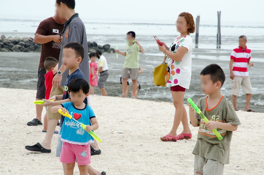 Kids playing on the beach with soap bubble