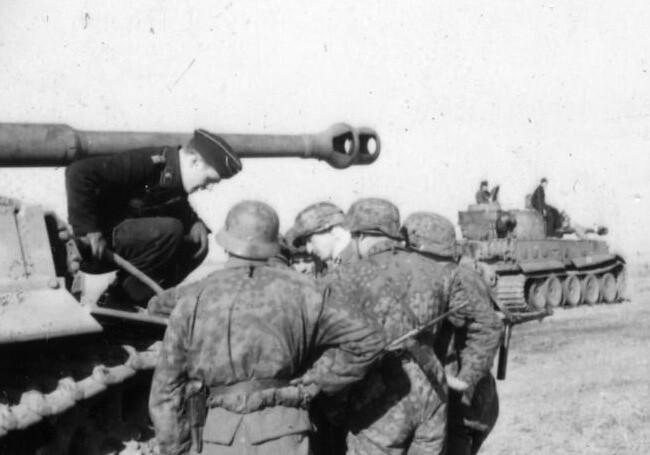 """Στρατιώτες Waffen SS συνομιλούν με τον αρχηγός ενός Panzer Mk VI """"Tiger""""."""