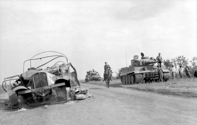 """Δυο άρματα μάχης Panzer Mk VI """"Tiger"""", ένα κατεστραμμένο όχημα και ένας Γερμανός έφιππος."""