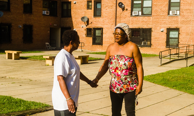 Deborah Nix, a local minister, shakes hands with Benning Terrace resident Pearl Speaks with Benning Terrace homes in the background.
