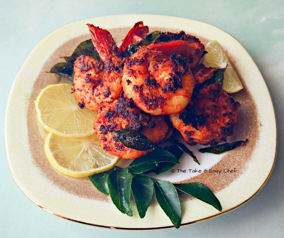 Chilli fried prawns with a garnish of curry leaves, and lime slices
