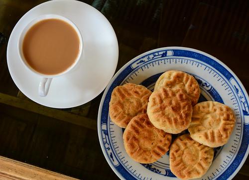 Cup of hot milk tea with sweet biscuit