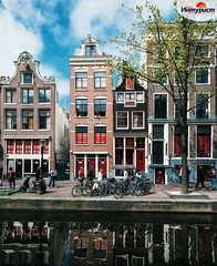 Typical narrow houses with large windows and canals with reflection, Amsterdam, Netherlands.