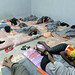 Dozens of migrants sleep alongside one another in a cramped cell in Tripoli's Tariq al-Sikka detention facility.
