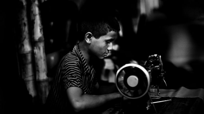 A young child sits working at a sewing machine.