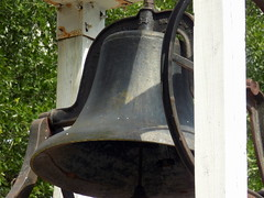 To ring a bell slowly (such as at a funeral)