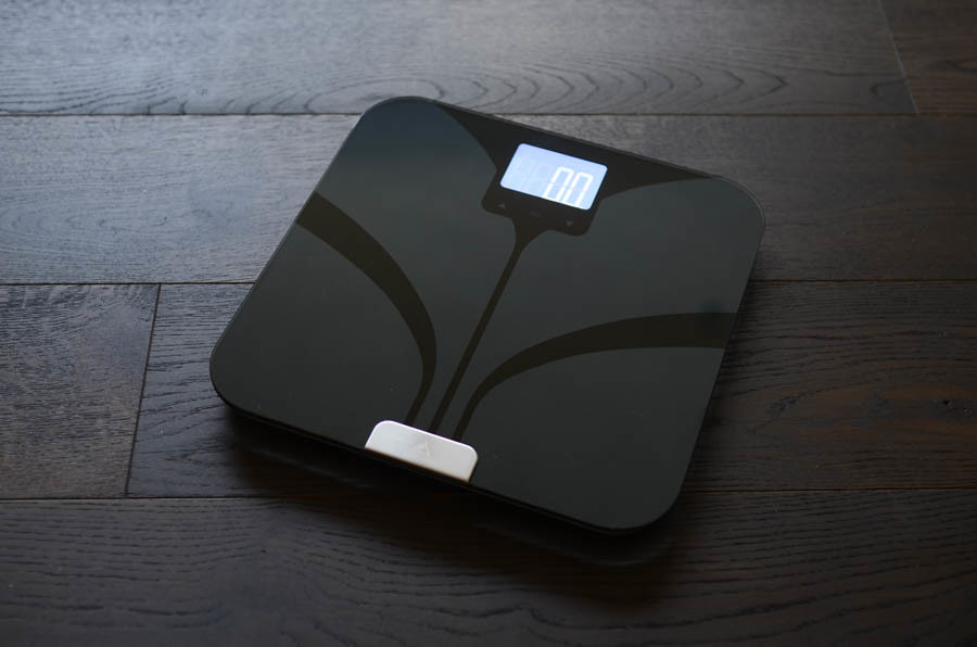 Weight Gurus black bathroom scale on wood floor