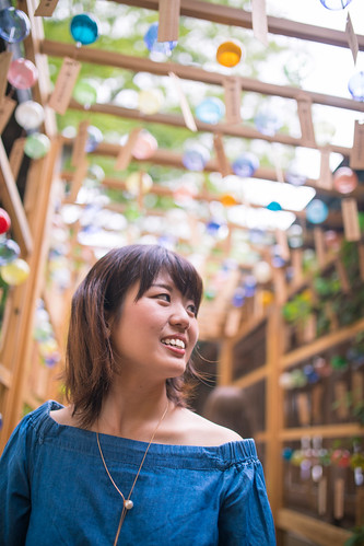 Young woman looking at Japanese wind chimes