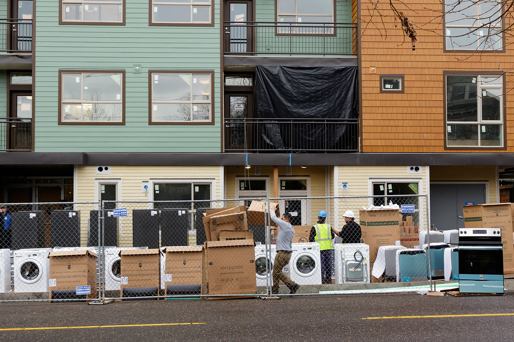 Washing machines and other appliances wait to be installed outside a new apartment building in Portland, Oregon