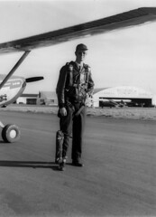 1954. Pilot John F. Wear demonstrates survival gear pack worn on leg during aerial forest insect detection surveys. Hillsboro Airport, OR.