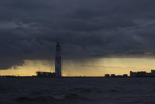 rain sunset tower building water coast cityscape seascape sky slouds storm skyline