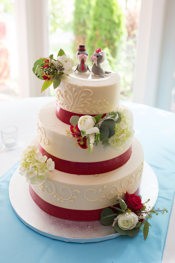 Wedding cake with red accents and walrus take topper.