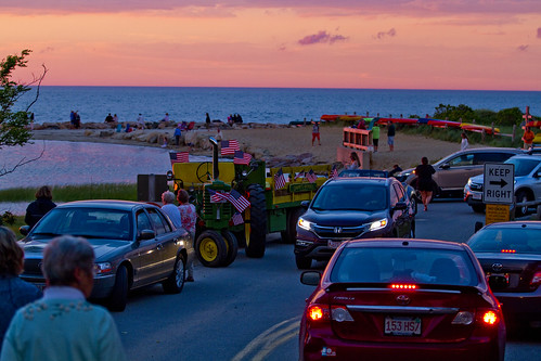 sunset beach people men women girls boys tourism travel sighsee view crowd group watch man woman tourist hayride cars parkinglot park lot boats kayak sea ocean skies bay