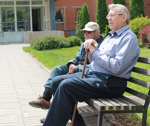Senior living community - 2 seniors sitting on a bench outdoors | by Senior Guidance