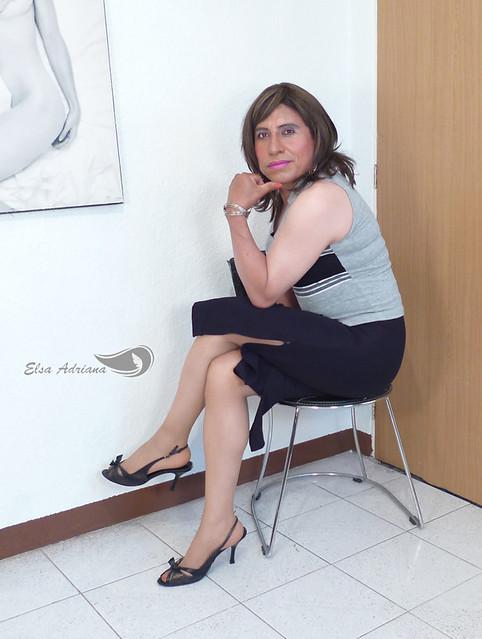 Black long skirt, light gray sleeveless blouse with black stripes, high heels and décolleté.