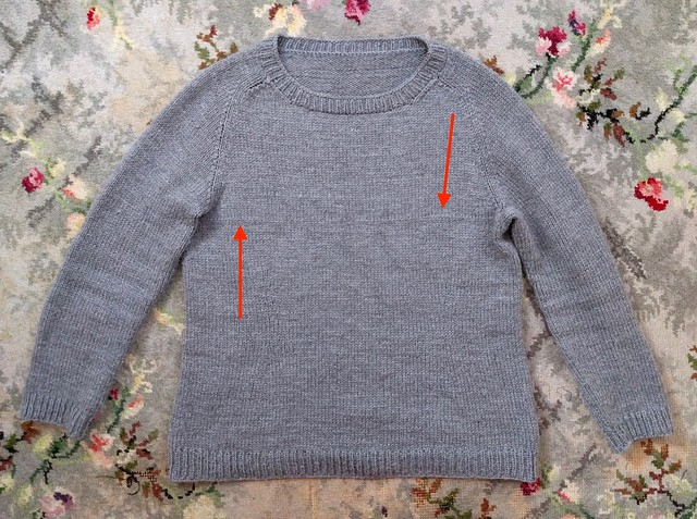 An image of a knitted jumper laid flat on a floral carpet. There are red arrows indicated a row where the tension is slightly loose.